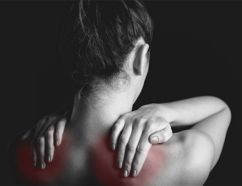 Woman rubbing sore shoulders, which are glowing red underneath her fingers. Indicates sore muscles from fibromyalgia.